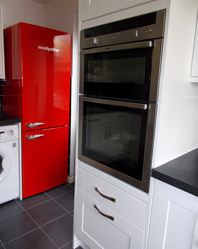 Ivory kitchen units, graphite metro tiles contrast with a vermillion fridge.