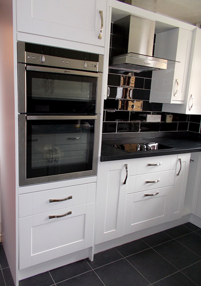 Contemporary ivory kitchen contrasted with charcoal metro tiles.